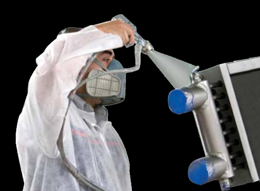 man spraying anti-corrosive spray on a heat exchanger