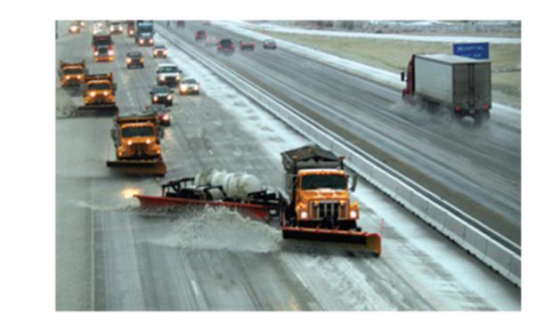 trucks plowing a highway