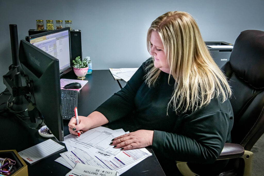 customer service staffer writing on paperwork at her desk at Active Radiator