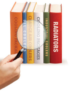 a hand holding a magnifying glass over various books about heavy equipment parts